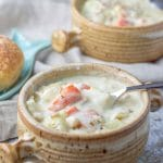 Spoon is in the crock of easy clam chowder. The chowder looks creamy and thick and you can see all the veggies!