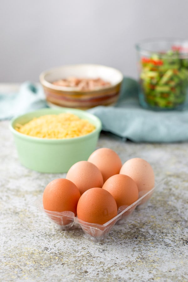 Eggs in a container, cheese in a green bowl, ham and asparagus in measuring bowls for the ham and asparagus quiche