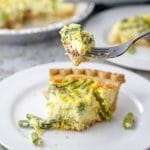 A forkful of the ham and asparagus quiche with the two quiches in the background