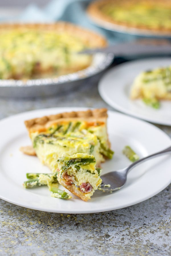 The forkful of ham and asparagus quiche on the front of the plate with the 2 quiches in the background