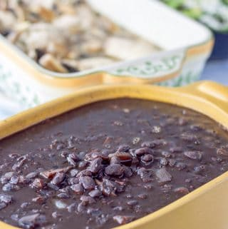 A casserole dish with the instant pot black beans filled to the brim. There is chicken in a baking dish in the background