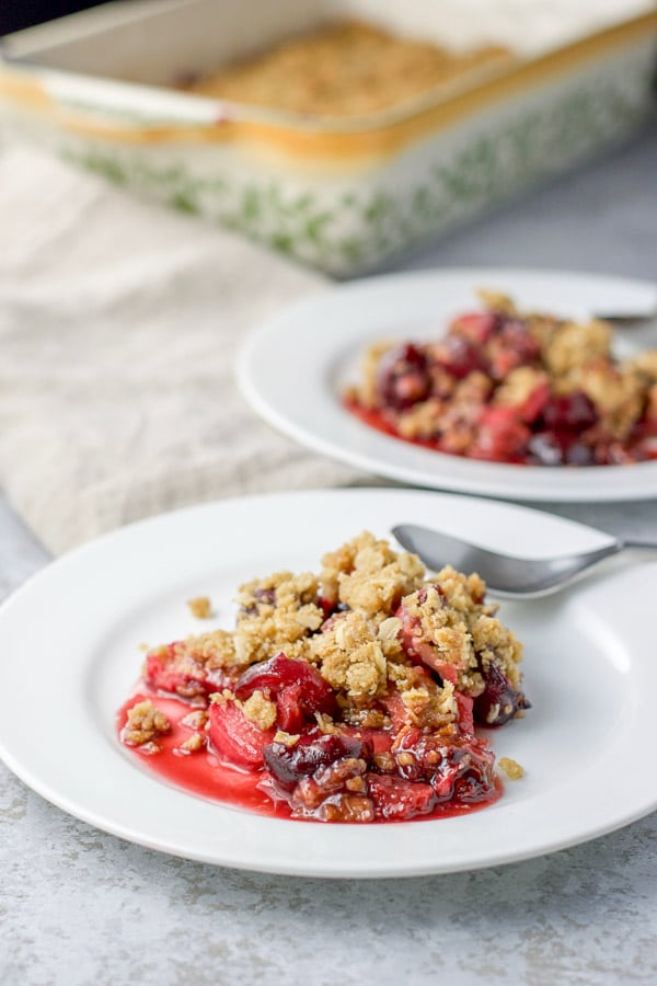 Another view of the two plates of cherry rhubarb crisp with the baking dish of crisp in the background