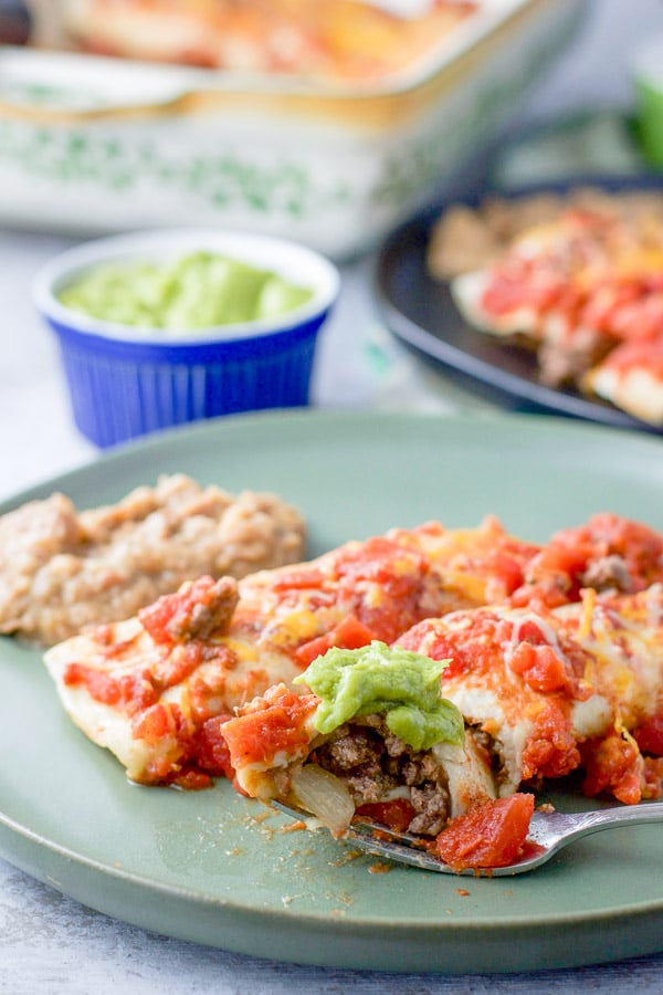 Forkful of enchilada on the plate also containing two enchiladas and a serving of refried beans. In the background is a ramekin of guacamole and another plate of enchiladas and refried beans.