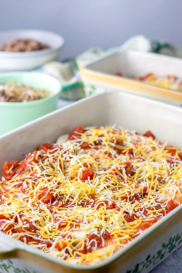Beef enchiladas lined up in a casserole baking dish and covered with red enchilada sauce and shredded cheese.