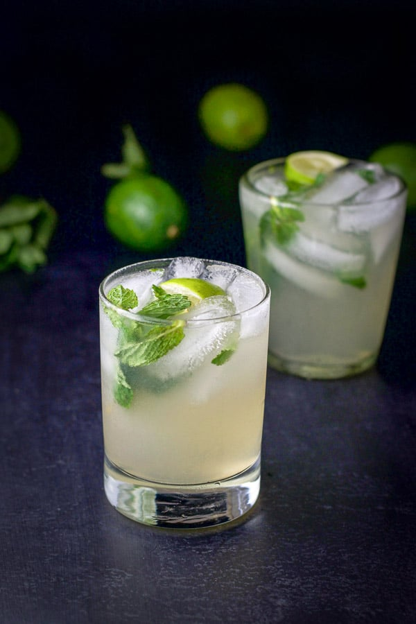 Two glasses of mojito cocktail recipe with limes and mint in the background