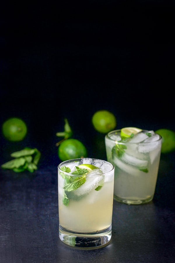 Different view of the Two glasses of mojito cocktail recipe with limes and mint in the background