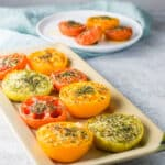Square photo of baked tomato halves on a rectangle plate and more on a round plate in the background