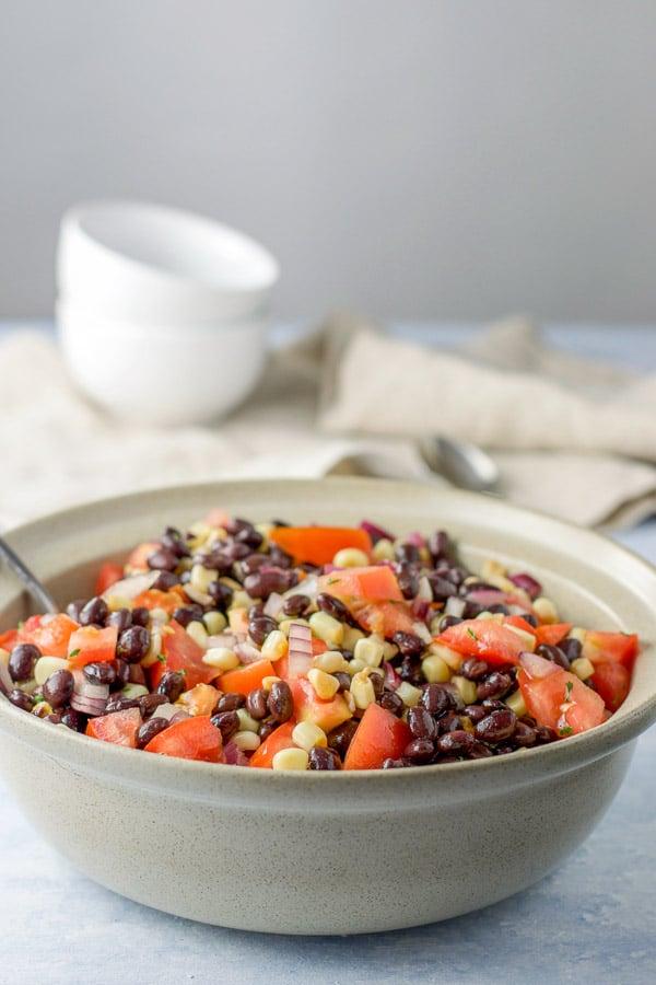 Big serving bowl of black bean salad with corn