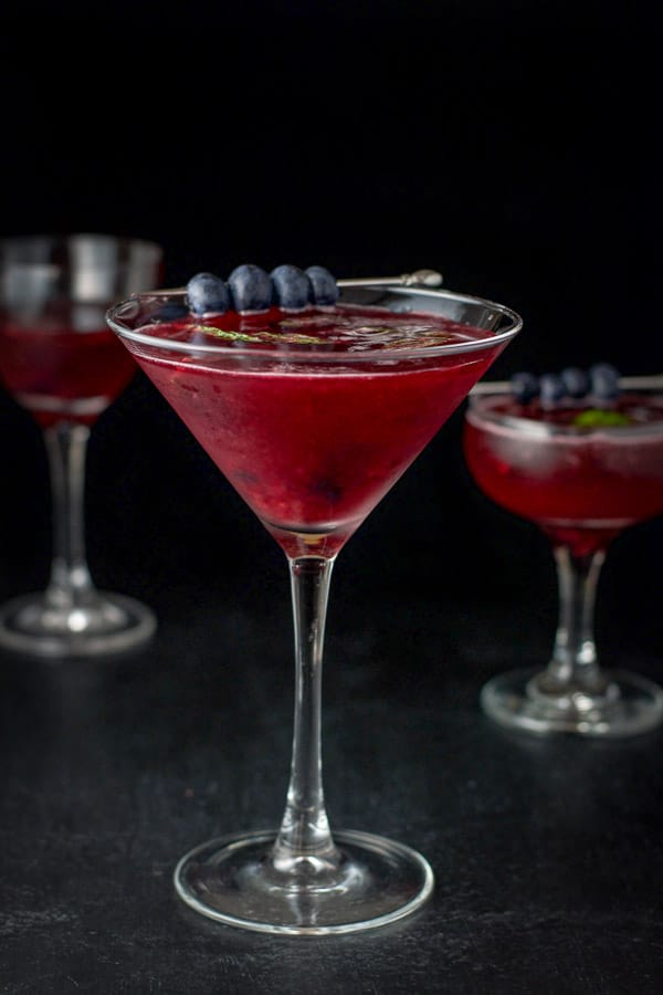 Martini glass in front with the blueberry mint cosmo