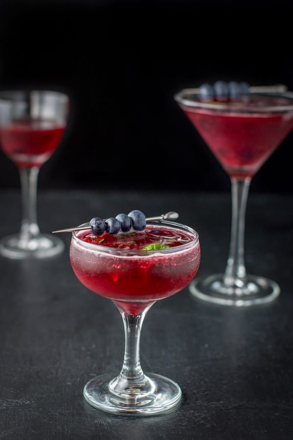 Coupe glass in front for the blueberry mint cosmo