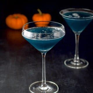 The witches brew cocktail in two martini glasses