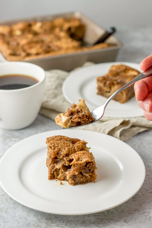 A forkful of apple walnut cake with the cake in the background