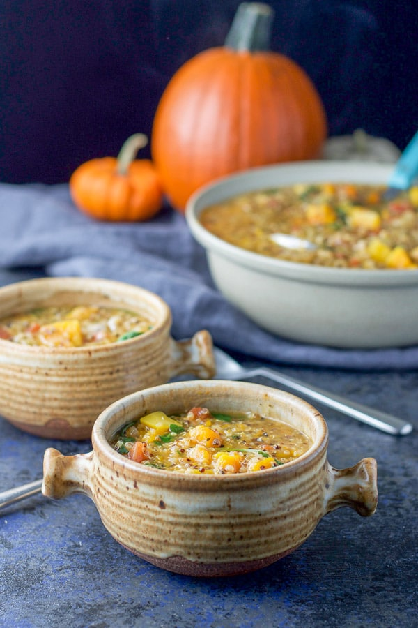 Two crocks filled with butternut squash stew with more in a nice serving bowl