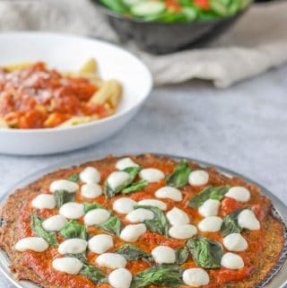 The cauliflower Margherita pizza with some pasta and a salad