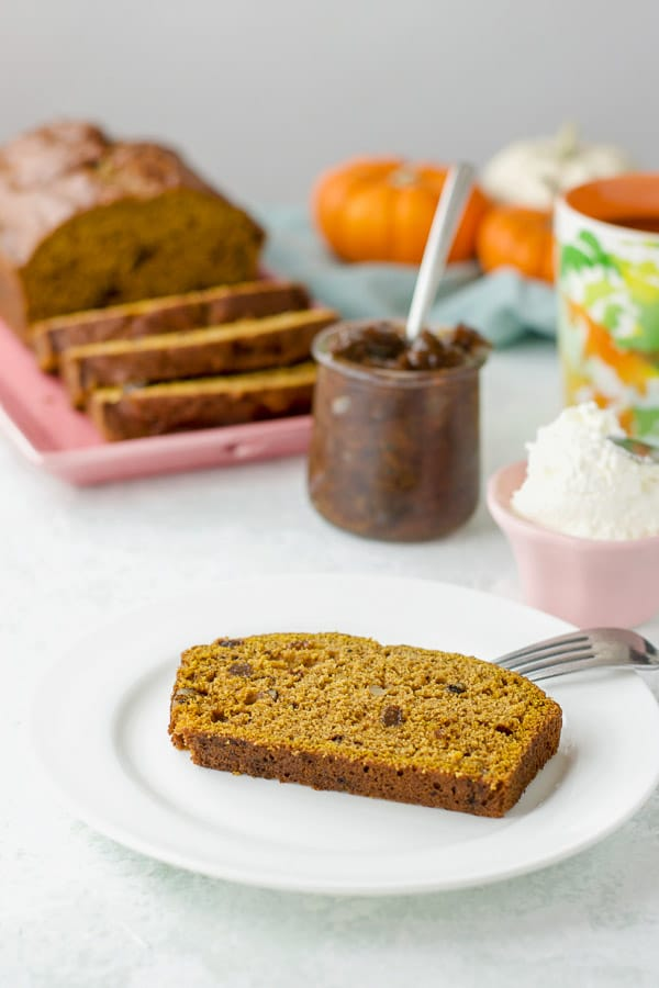 A slice of easy pumpkin bread on a plate with some spreads in the background