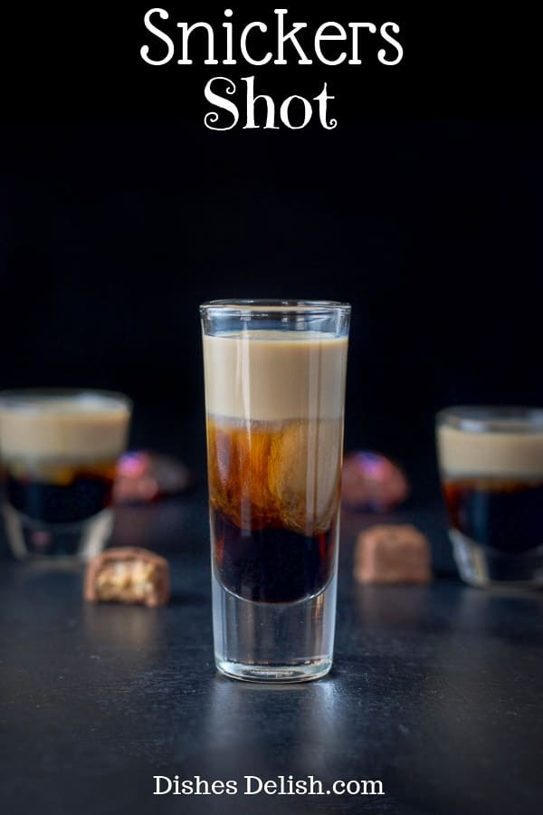 This Snickers shot has only three ingredients:  Kahlúa, Frangelico and Baileys Irish cream!  So delicious and reminiscent of the famous candy bar! #snickersshot #layeredshot #dishesdelish