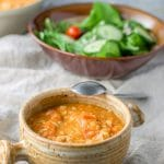 Tuscan white bean soup ladled into a crock with a salad in the background