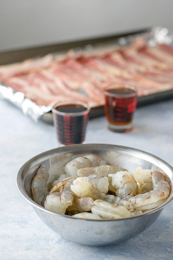 Shrimp, maple syrup, soy sauce and bacon on a pan for the bacon wrapped shrimp