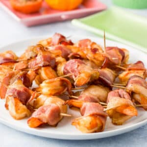 A close up of the bacon wrapped shrimp on a plate