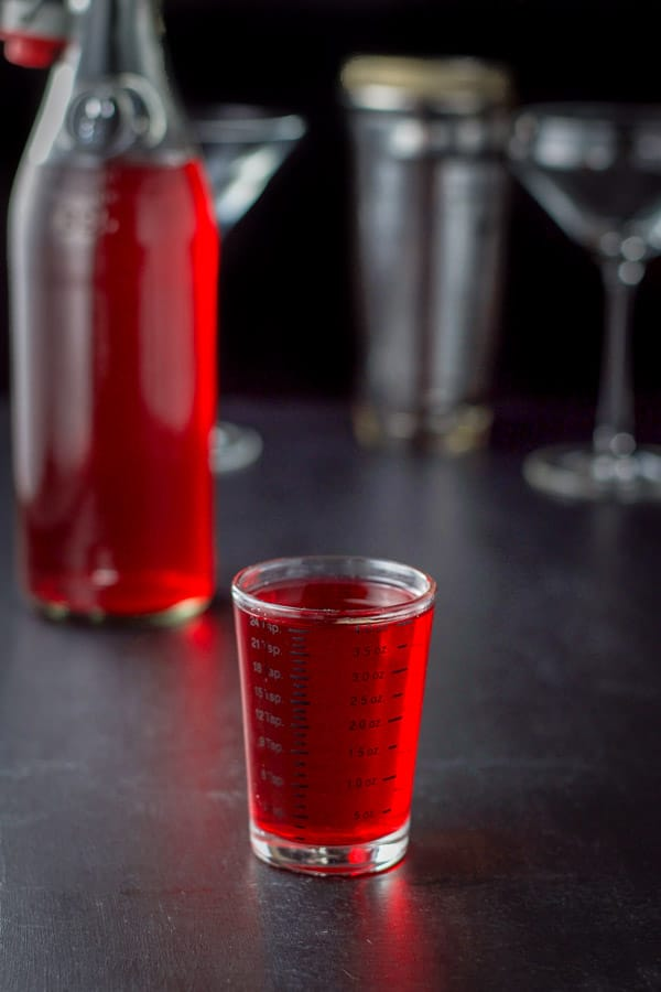 Cranberry infused vodka poured out for the cranberry cosmo