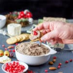 A male hand holding a cracker of the chicken liver pate recipe