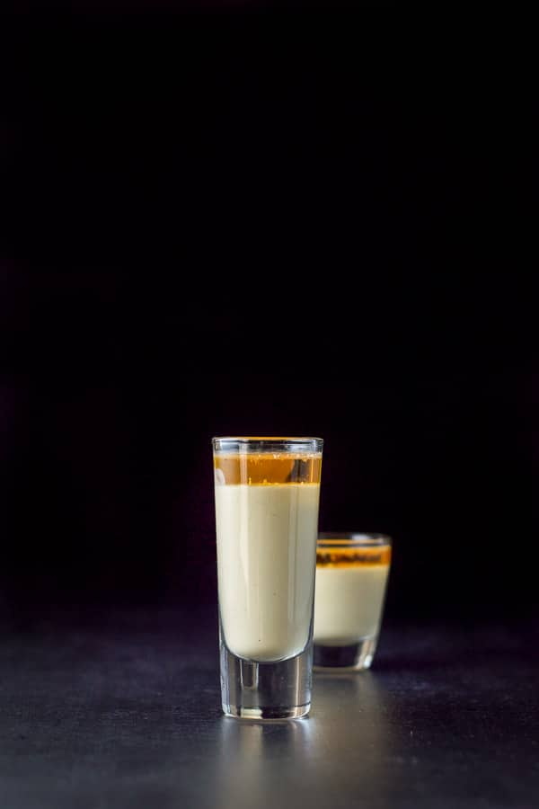 Vertical view of the eggnog shot with the tall glass in front