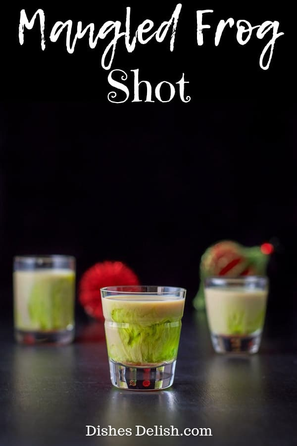 This weirdly named shot has 3 ingredients, Midori, Baileys and a dash of grenadine and is not only pretty but decidedly delicious! #layeredshot #mangledfrogshot #dishesdelish