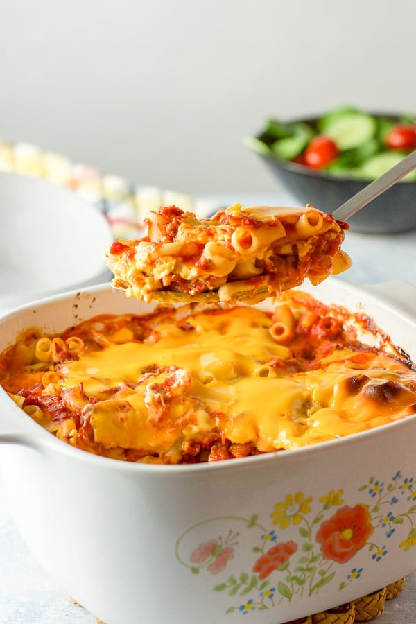 A big spoonful of bacon tomato pasta held over the casserole