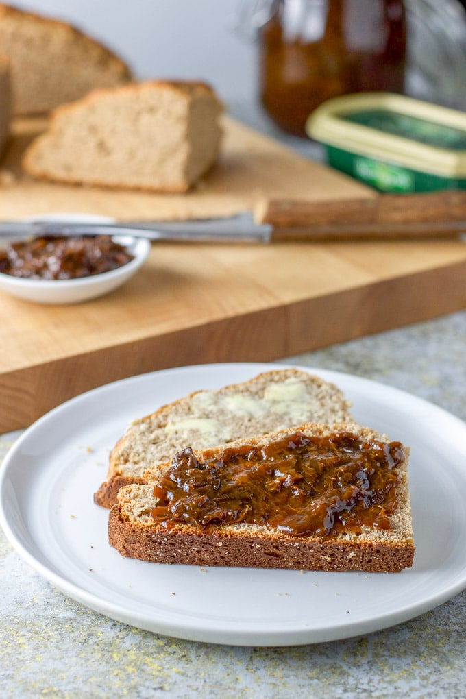 Prune spread on the brown Irish soda bread in front and a piece with butter in the back