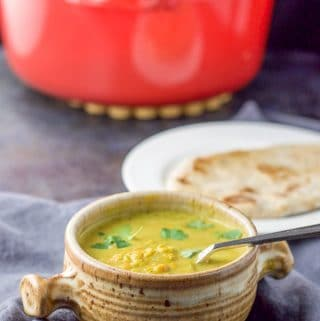 A crock full of coconut curry lentil soup with naan in the background