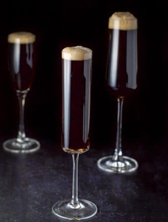 Three champagne flutes filled with Guinness red velvet cocktail