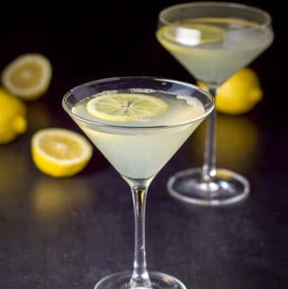 The lemon drop martini with lemons in the background