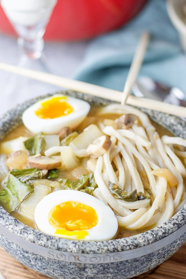 Close up of the udon noodle soup with the egg in the bowl