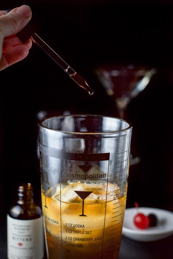 Bitters being dripped into the bourbon Manhattan