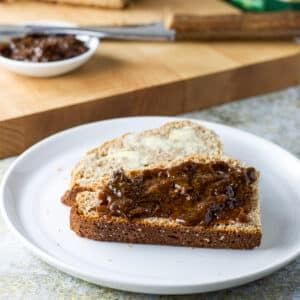 Two pieces of bread, one with prune spread the other with butter in front of a cutting board and knife