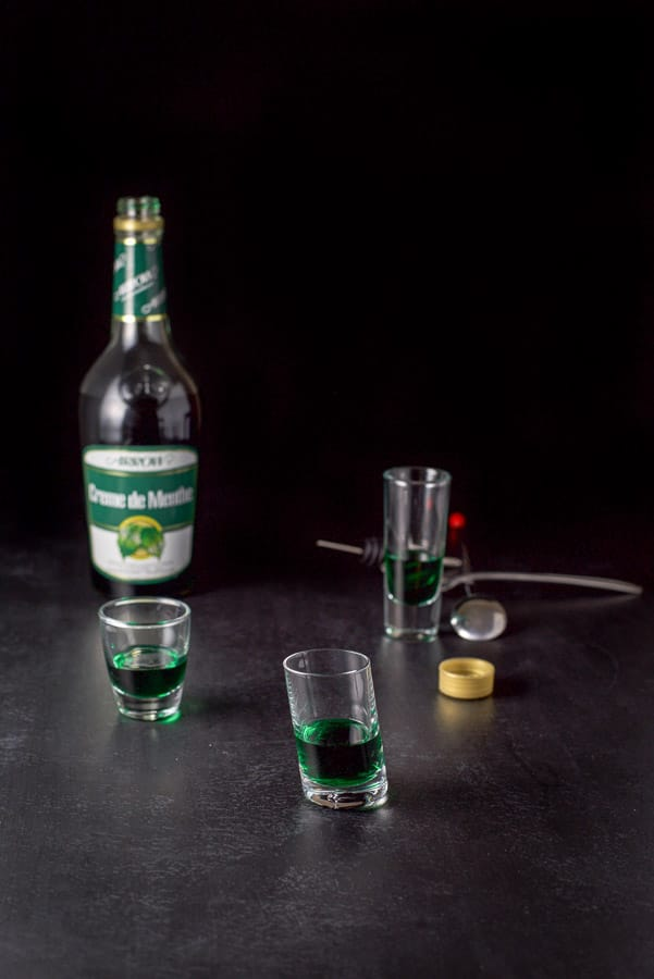 Green creme de menthe poured into the shot glasses for the Irish flag shot