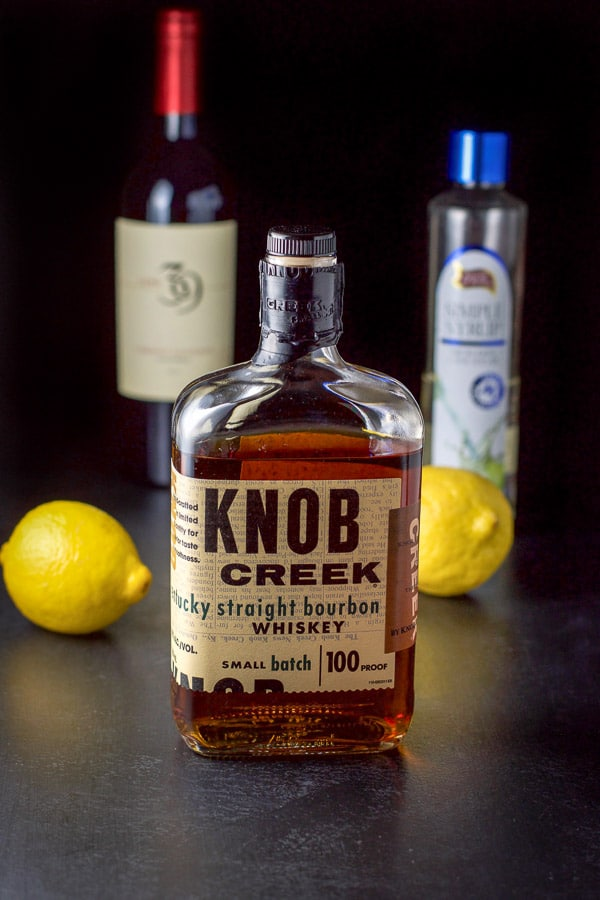 The ingredients for the New York Sour cocktail - bourbon, lemon, simple syrup and wine