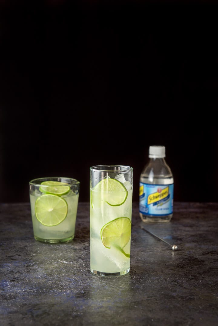 The gin and lime mixed into a glass waiting for the club soda for the gin lime rickey