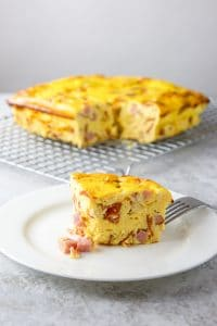 A slice of pizza gana on a plate with the casserole behind it