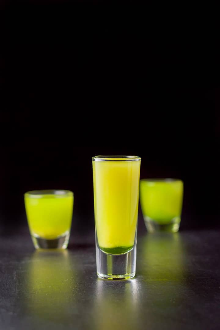 Vertical view of the melon ball shot with the tall glass in front