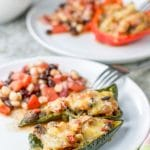 Baked stuffed peppers on a plate with some bean salad