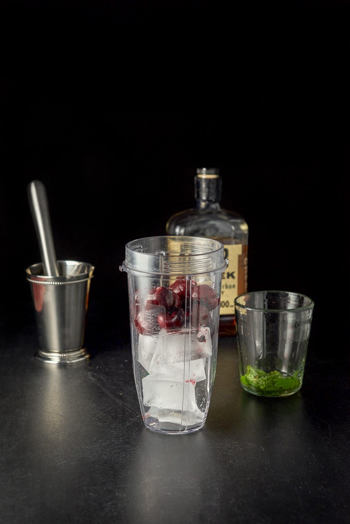 Ice cubes and pitted cherries in a blender container for the cherry mint julep