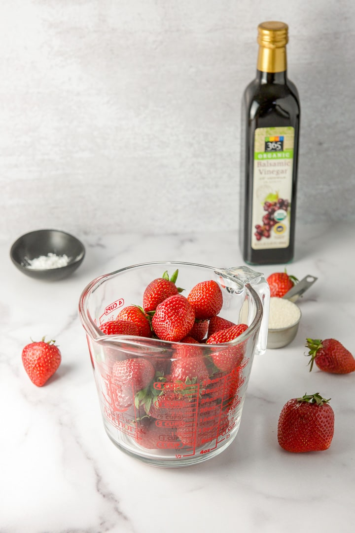 Strawberries in a measuring glass, sugar, corn starch and balsamic vinegar for the strawberry sauce