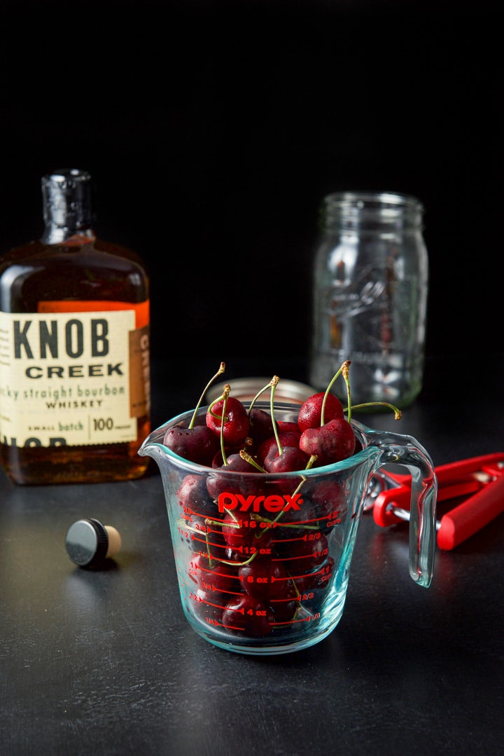 Cherries in a measuring cup, bourbon and a jar for the cherry infused bourbon