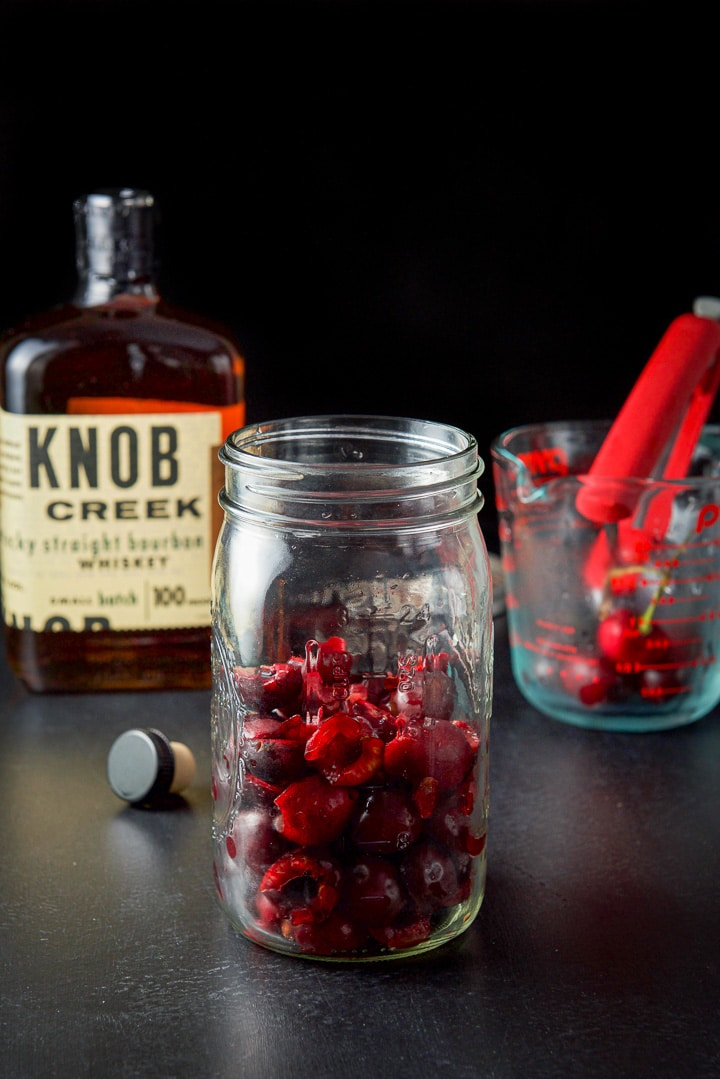 Pitted and halved cherries in a jar for the cherry infused bourbon