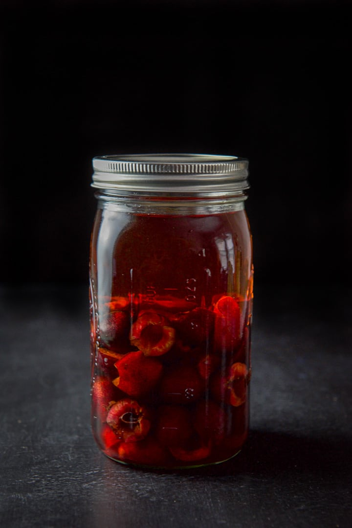 Cherry infused bourbon capped in a jar ready to rest