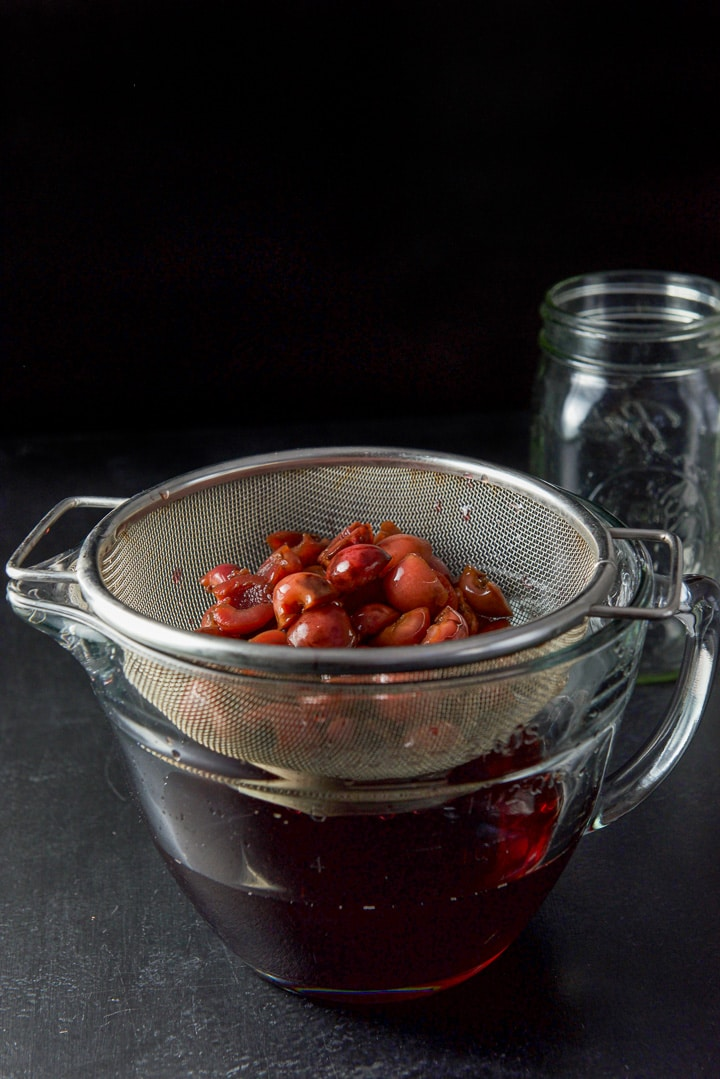 Cherries in a sieve over a bowlful of cherry infused bourbon
