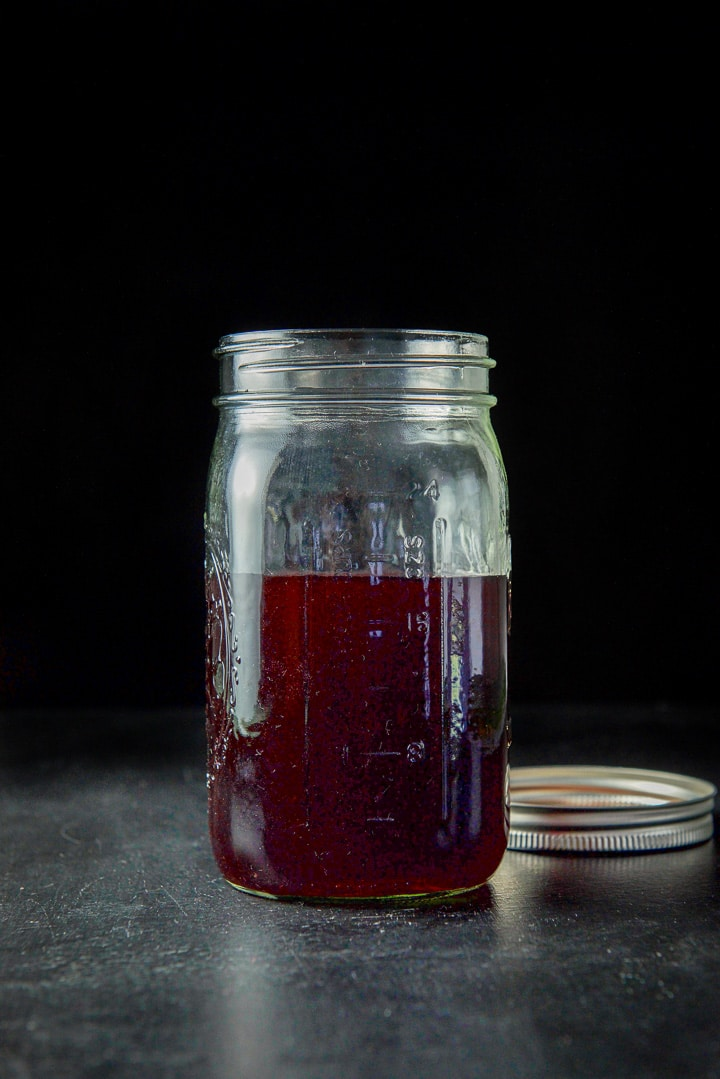 Glass jar filled with cherry infused bourbon