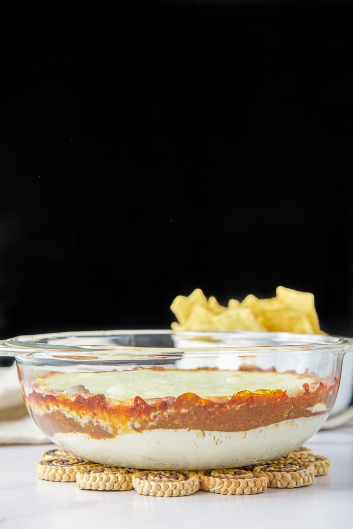 Vertical view of the chili cheese dip in a see through dish