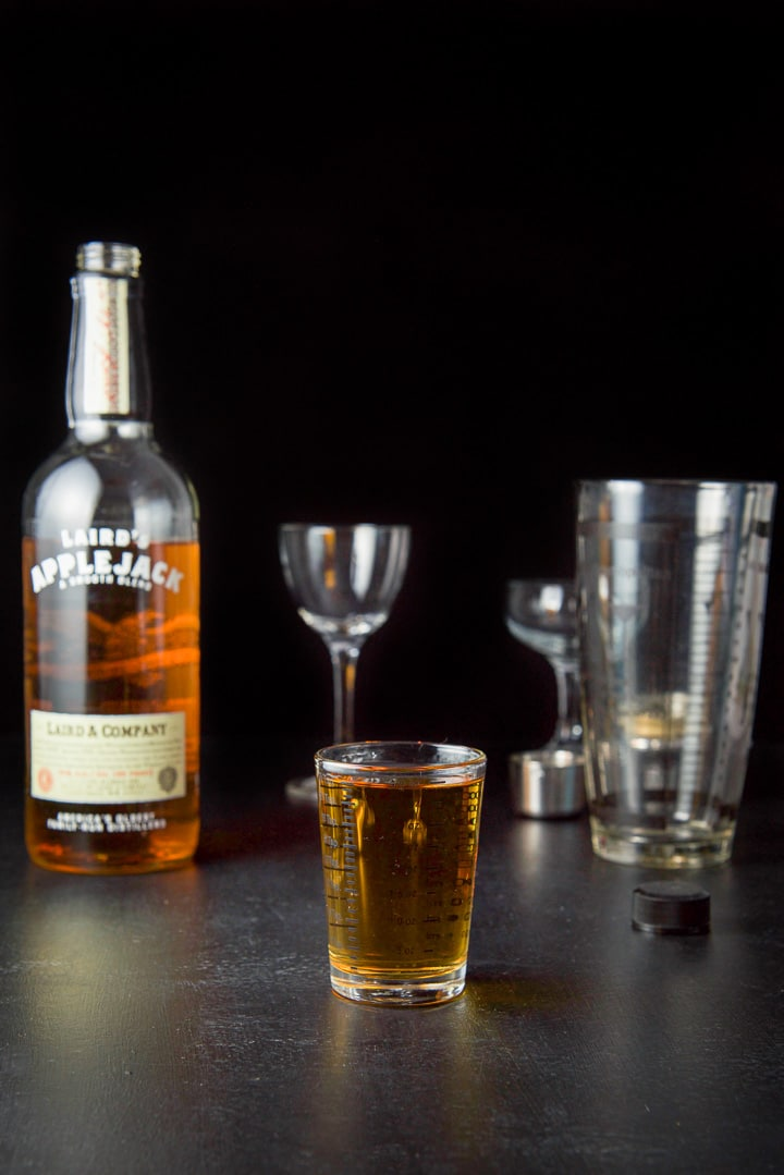 AppleJack liquor measured for the pink lady cocktail